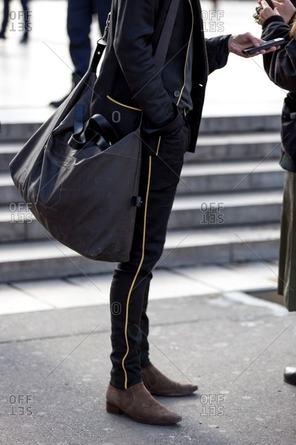 Paris, France - October 10, 2015: Fashionable man wearing black and gold outfit carrying a large bag