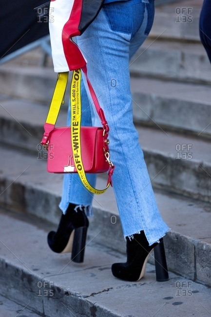 Paris, France - October 10, 2015:  Woman wearing cut-off jeans and carrying a designer purse