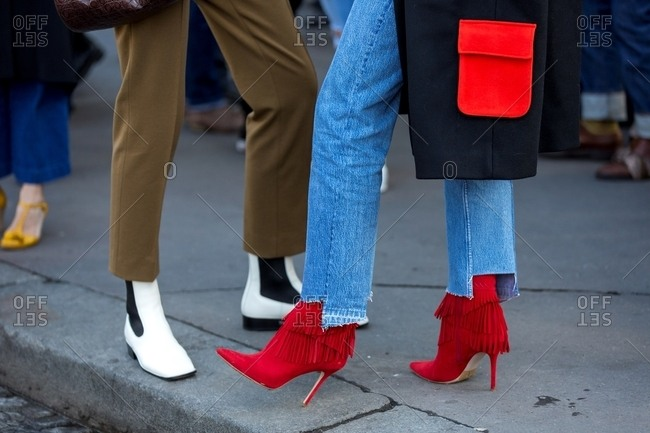 Paris, France - October 10, 2015:  Woman wearing cut-off jeans and red heels