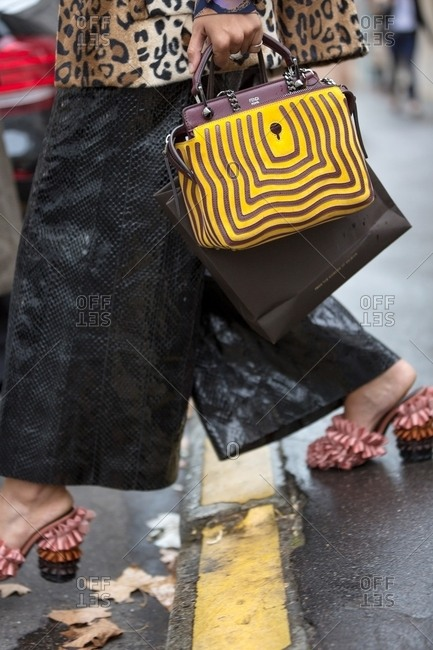 Paris, France - October 10, 2015: Fashionable woman carrying brown and yellow purse