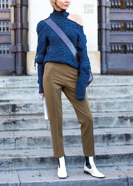 Paris, France - October 10, 2015: Woman wearing a blue cold-shoulder sweater and tan pants