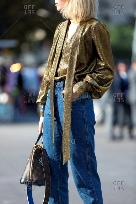 Paris, France - October 10, 2015: Woman wearing a gold blouse and jeans