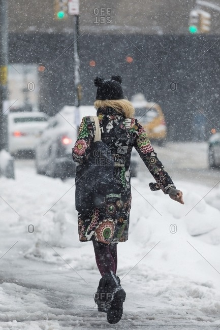 New York - February 9, 2017: Rear view of woman walking on city street in snowy weather