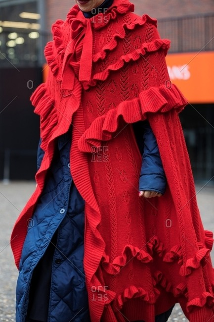 London, England - February 18, 2017: Woman wearing long red sweater over a navy blue coat