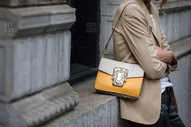 New York - September 13, 2017: Woman wearing tan jacket and designer purse