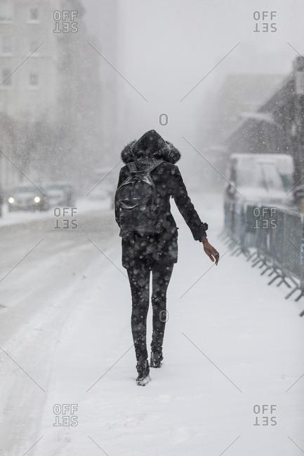 Woman walking solo in urban snowstorm