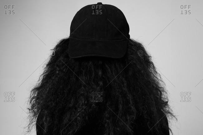 Dark outline of woman with cap from behind