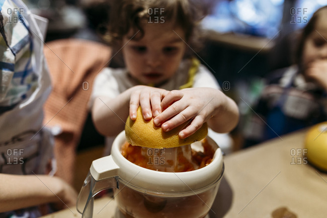 Little girl juicing an orange