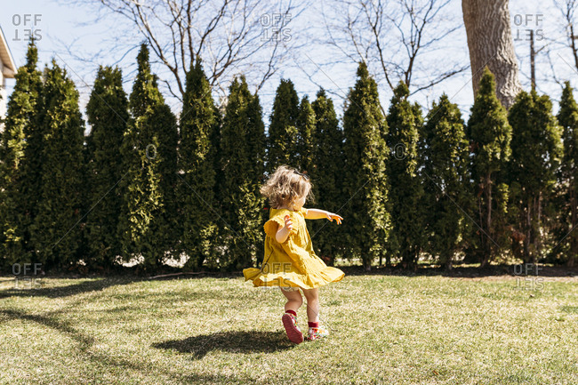 Little girl twirling in yard