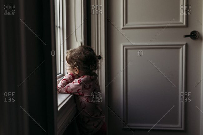 Little girl wearing pajamas looking out window