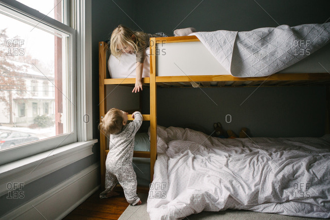 Girl reaching toward baby sister from top of bunk beds