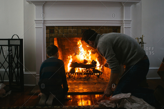 Boy sitting next to fireplace as father uses fire iron