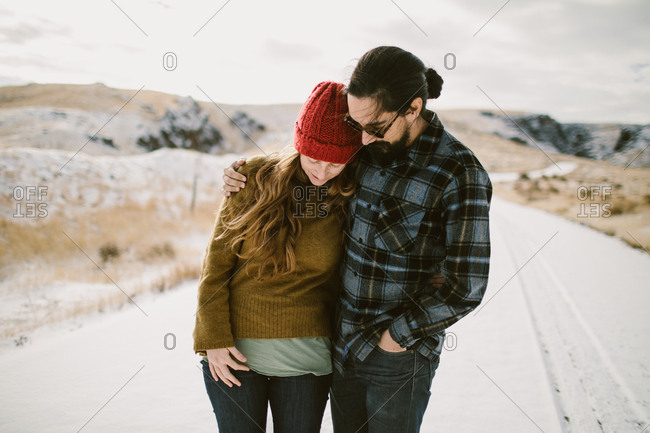 Man with his arm around woman on snowy winter day