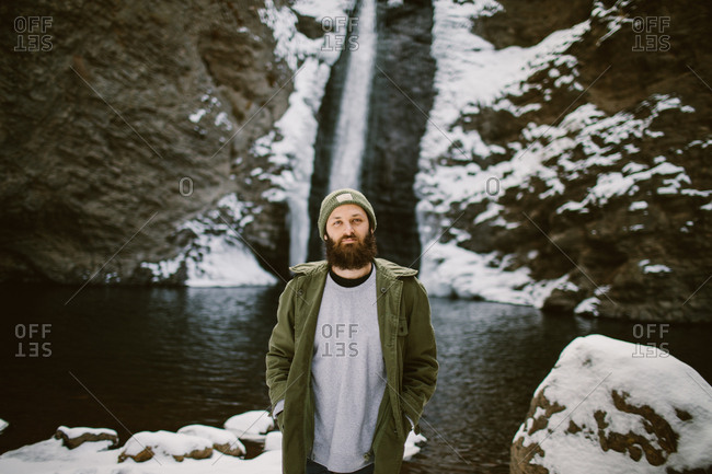 Man standing in front of a winter waterfall