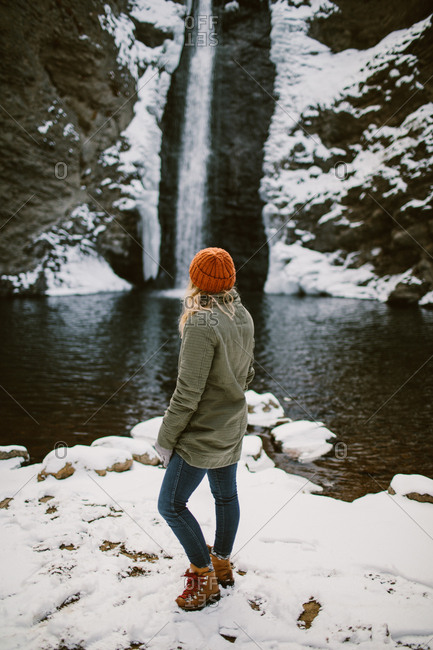 Woman standing in front of a winter waterfall