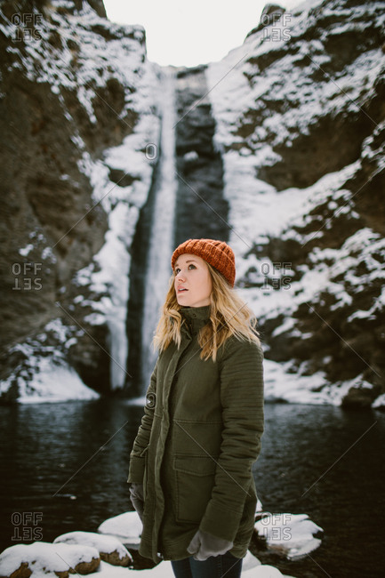 Woman standing in front of a snowy waterfall
