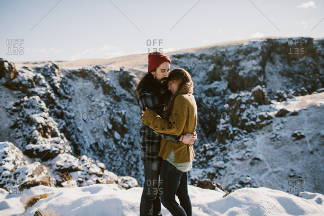 Young husband and wife hugging  in the snow