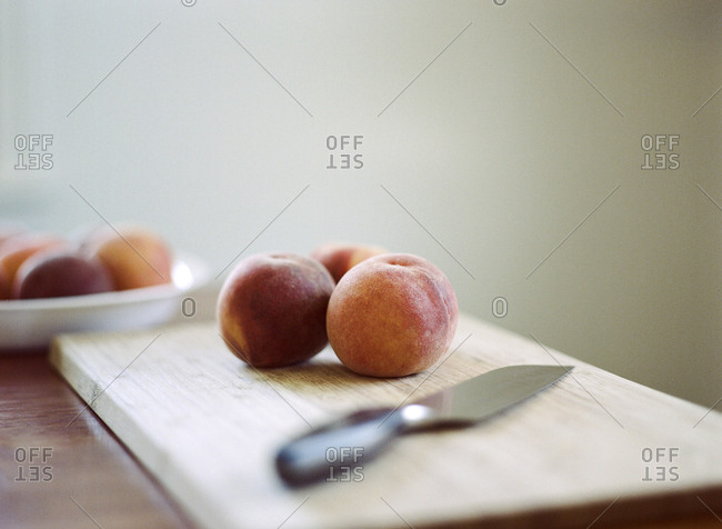 Fresh peaches and knife on cutting board