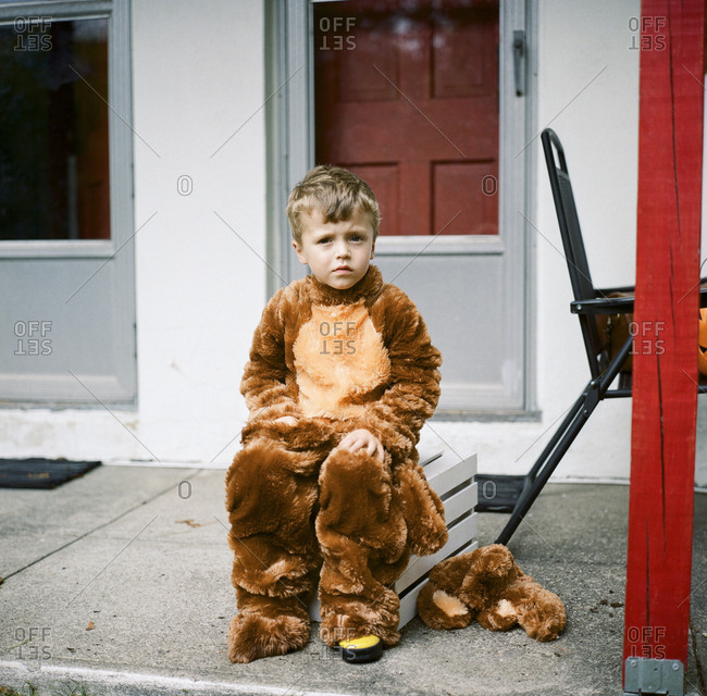 Little boy in Halloween costume sitting on wooden crate