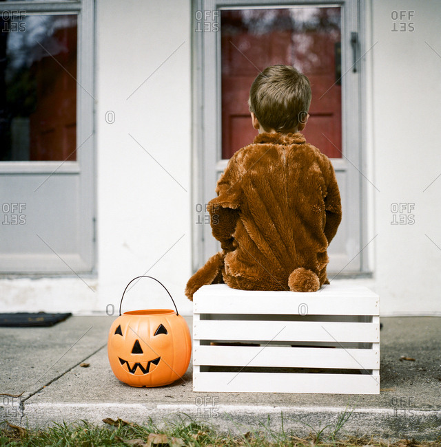Child in Halloween costume sitting on wooden crate