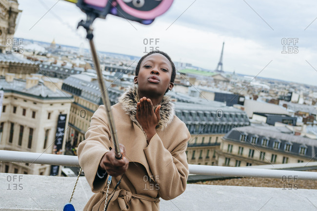 Young woman taking a selfie with a selfie stick with the city of Paris and the Eiffel Tower in the background