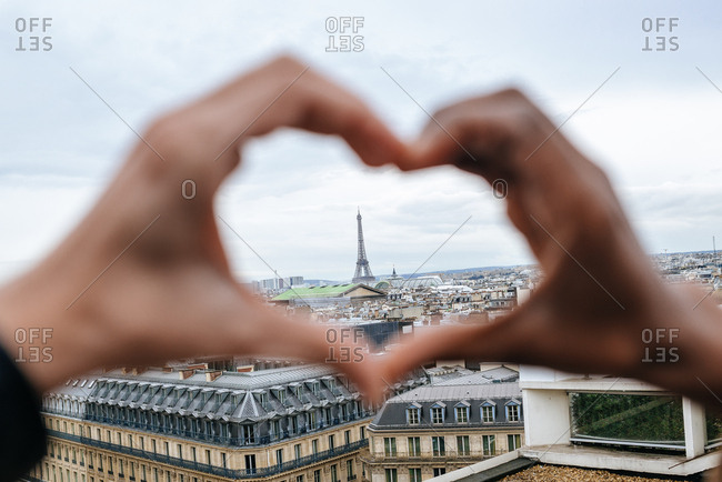 Hands of woman and man forming a heart with the Eiffel Tower inside