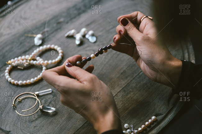 Person making a beaded bracelet