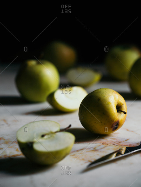 Green apples and knife on marble counter