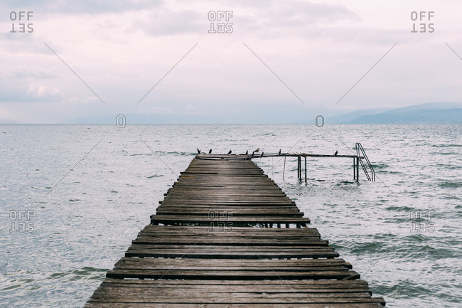 Old wooden pier at the shore of a lake