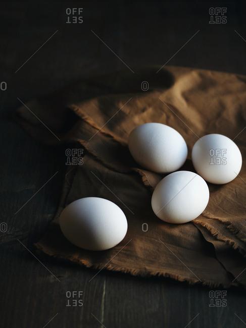 Four fresh white eggs on a brown cloth