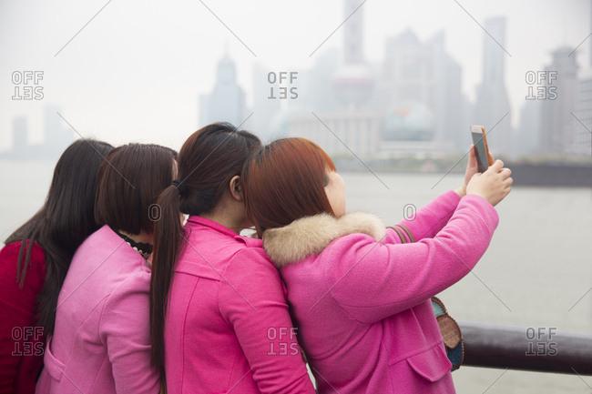Group of women in matching pink taking selfie on the Bund in Shanghai