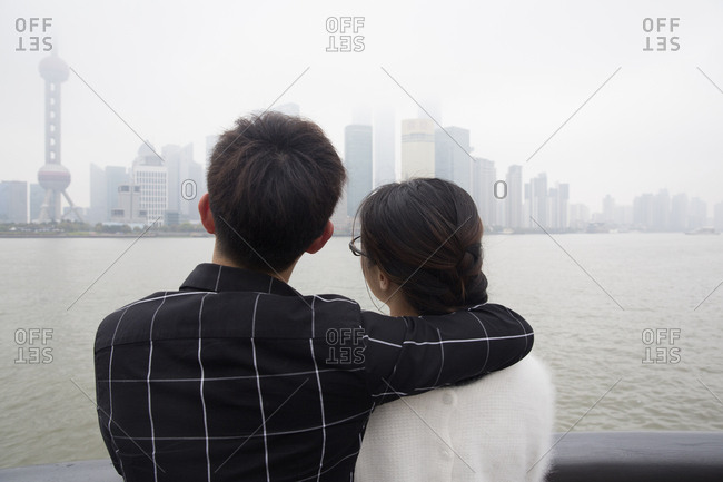 Rearview of young couple looking out over river to Pudong from the Bund in Shanghai