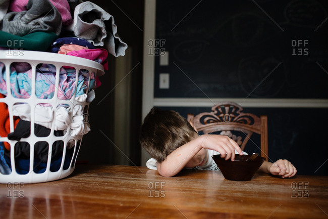 Young boy laying head on table refusing to eat breakfast