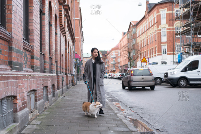 Young woman walking dog on a city street