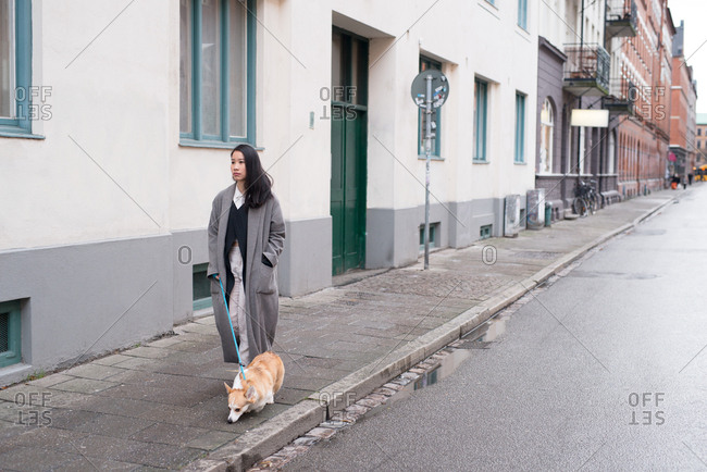 Young woman walking dog on quiet city street