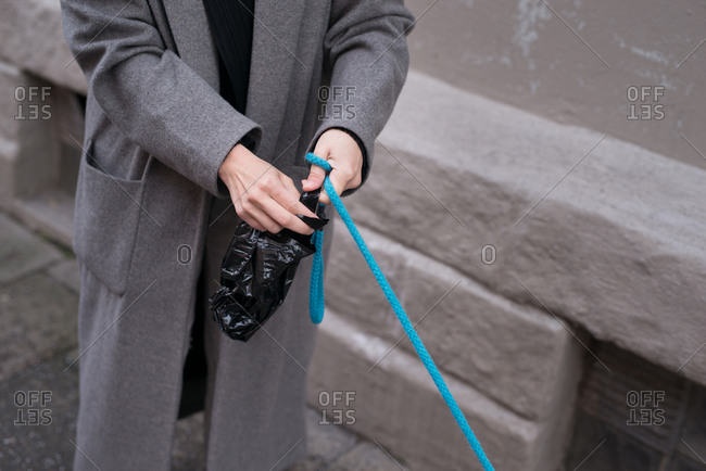Woman bagging dog poop during a walk in the city