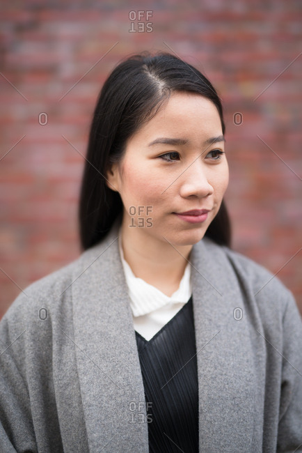 Extremely shallow depth of field portrait of young woman with black hair looking off camera in front of a brick wall