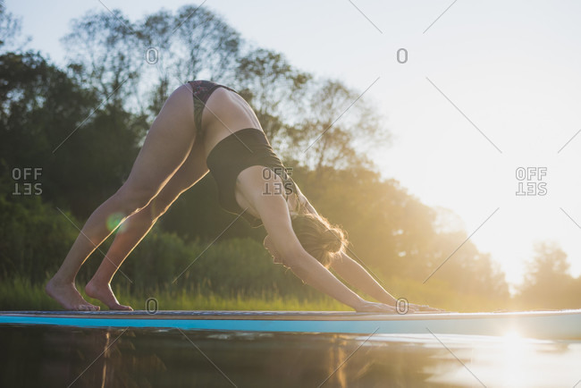 Young woman doing SUP yoga at golden hour
