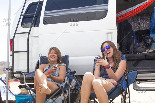 Two friends at music festival sitting outside van and showing henna tattoos, San Bernardino County, California, USA