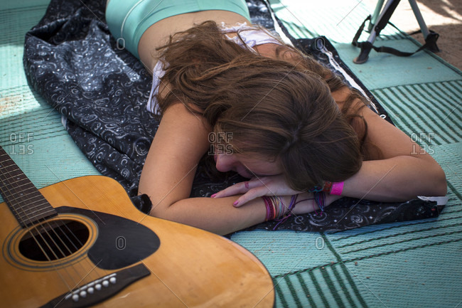 Female festival goer sleeping next to guitar in tent, San Bernardino County, California, USA