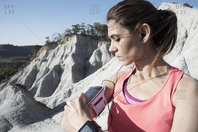 Woman wearing sportswear using smartphone in armband, Gurb, Barcelona, Catalonia, Spain