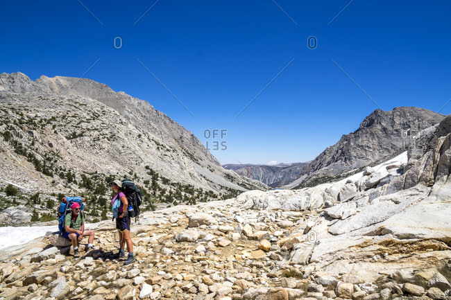 Man and woman resting while hiking at Piute Pass in Eastern Sierra, Bishop, California, USA