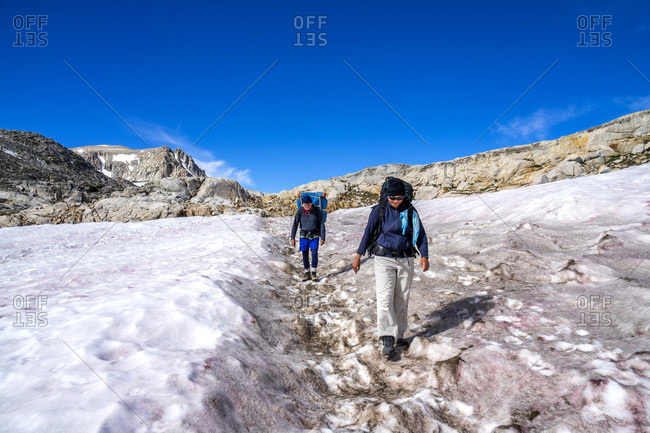 Man and woman hiking across snow field down Piute Pass in the Eastern Sierra, Bishop, California, USA