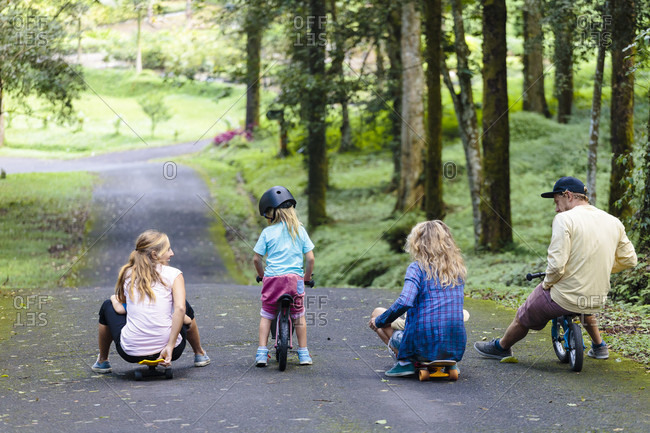 Family with skateboards and bicycles playing in park, Bedugul, Bali, Indonesia