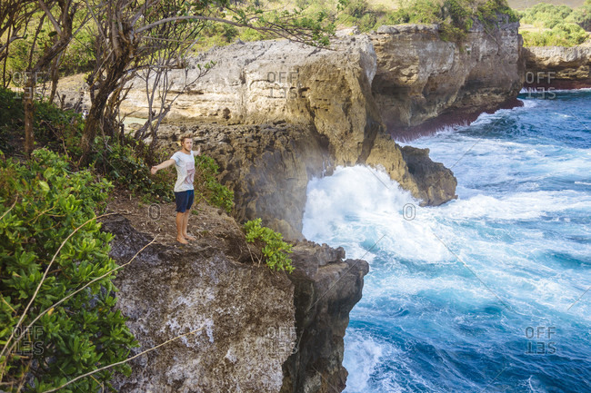 Adult man standing on coastal cliff and spreading arms, Bali, Indonesia