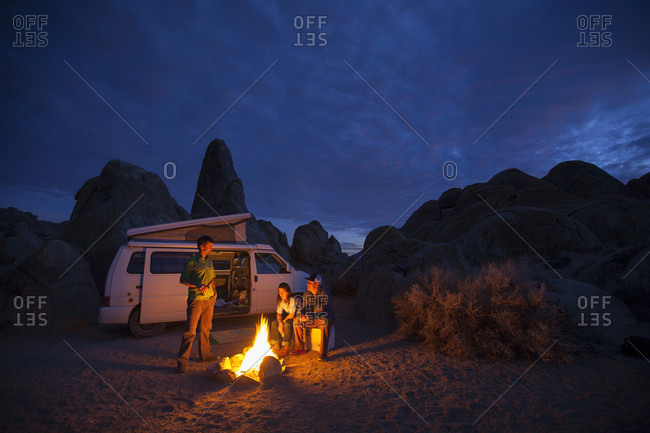 Group of friends around campfire at night while camping in Alabama Hills Recreation Area, Lone Pine, California, USA