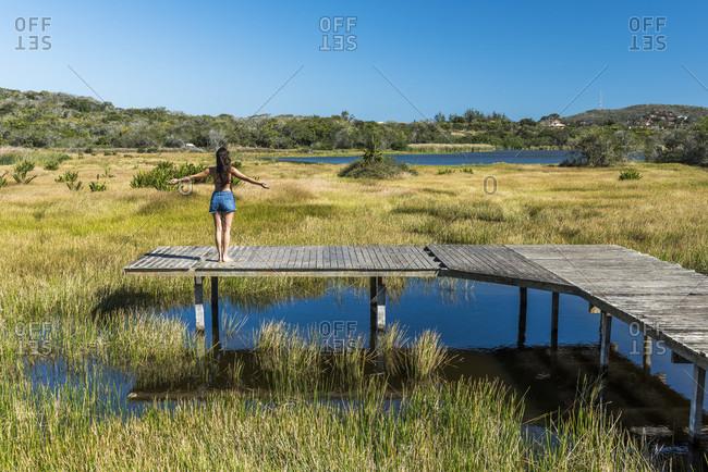 Woman with open arms on pier by lagoon in Buzios, Rio de Janeiro, Brazil