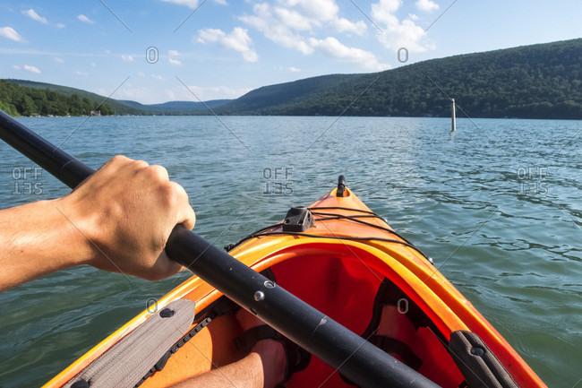 POV of man paddling in kayak on Skaneateles Lake, Skaneateles, New York State, USA