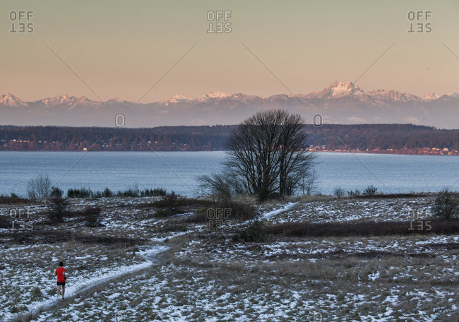Person jogging in winter at sunset in Discovery Park, Seattle, Washington State, USA
