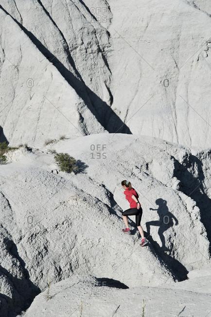 Woman running through arid zone, Gurb, Barcelona, Catalonia, Spain